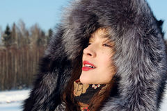 Girl in fur coat with hood Stock Images
