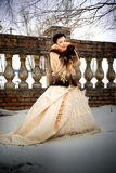 Girl in a fur coat and lush vintage dress in winter forest Royalty Free Stock Images