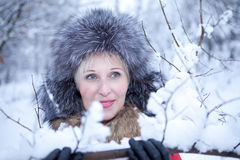 Girl in fur coat poses girl on snow Royalty Free Stock Image