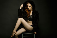 Girl in a fur coat. With red hair sitting on a chair Stock Photo