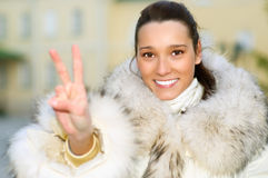 Girl in fur coat shows victory Royalty Free Stock Photos