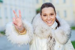Girl in fur coat shows victory Stock Photography
