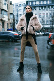 The girl is in a fur coat on the street. In the rain Stock Images