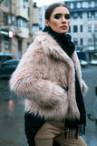 The girl is in a fur coat on the street. In the rain Stock Photo