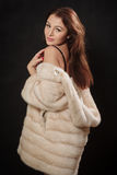 Girl in fur. Coat undressing on black background Royalty Free Stock Images