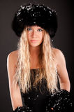 Girl with fur hat. Studio shooting,black background,slavic girl with black fur hat,decoration of snowflakes Royalty Free Stock Photo