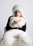Girl in a fur hat with a bear Stock Images
