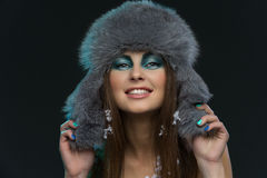 Girl in fur hat with snow. Portrait of smiling beautiful girl in fluffy fur hat with snow Royalty Free Stock Photos