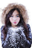 Girl with fur jacket blowing snow Stock Image
