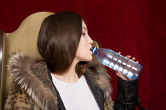 The girl in a fur jacket drinking water from a bottle Stock Photos