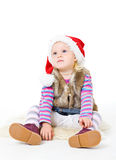 Girl in a fur jacket and a red Santa's cap Stock Images