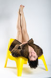 Girl in fur on plastic chair Royalty Free Stock Photos