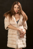 Girl in fur. Tan girl in fur coat undressing on black background Stock Photos