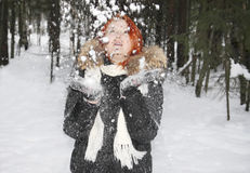 Girl with fur throws up snow in woods at winter Stock Photos
