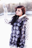 Girl in a fur vest catches snow Royalty Free Stock Photos