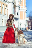 The girl in a fur vest and red dress walking with dog Stock Images