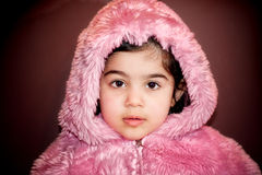 Girl in furry jacket. A close-up portrait of a two year old in pin furry jacket Royalty Free Stock Images