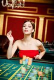 Girl gambles at the gambling house Stock Photo