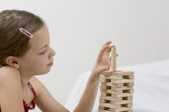 Girl / game / white. Girl measuring the block. Focus on the blocks Royalty Free Stock Photography