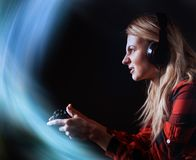 Girl gamer in headphones and with a joystick in her hands playing network games preparing to participate in international competit. Ions in e-sports Royalty Free Stock Images