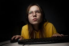Girl gamer sits at a laptop at night at home, a student plays games, she loses and wins