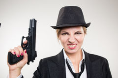 Girl gangster holding a gun. Classic suit and hat. Royalty Free Stock Photos