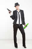 Girl gangster holding a gun. Classic suit and hat. Stock Photography