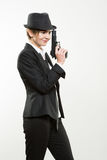 Girl gangster holding a gun. Classic suit and hat. Royalty Free Stock Photography