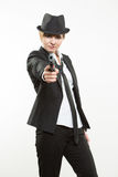 Girl gangster holding a gun. Classic suit and hat. Beautiful girl gangster holding a gun. Classic suit and hat. isolated on white background. red nail polish Royalty Free Stock Image