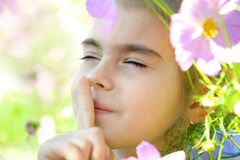 Girl in Garden. Cute girl with a finger on her lips, in flowers Stock Image