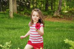 Girl in Garden. Cute little girl running through the garden holding a bouquet of flowers Stock Photo
