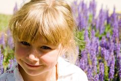 Girl in a Garden. A cute girl in the sunshine with a flower garden behind her Royalty Free Stock Photos
