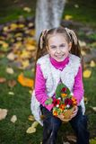 Girl in the garden with an autumn bouquet of flowers on a background of green grass. royalty free stock photo