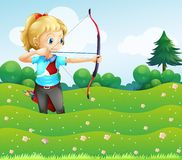 A girl at the garden holding a bow and an arrow Stock Images