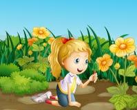 A girl in the garden holding a shovel Stock Photos