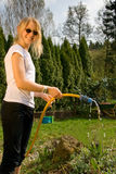 Girl with garden hose Stock Image