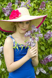 Girl in Garden of Lilacs. Girl showing off her newly picked Lilacs in garden while wearing huge brim sunhat Stock Photos