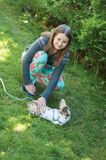 A girl in a garden patting a lying on the grass rabbit with a leash. Over background of bushes Royalty Free Stock Photo