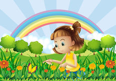 A girl at the garden with a rainbow at the back Royalty Free Stock Image