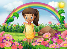 A girl in the garden with a rainbow at the back Royalty Free Stock Image