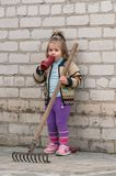 Girl with a garden rake Royalty Free Stock Images
