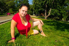 A girl in the garden. Girl sitting on the grass in the garden stock images