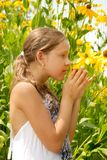 Girl in garden smells yellow flower Royalty Free Stock Image