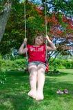 Girl on garden swing Stock Photography
