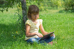 Girl in the garden with the tablet. Conducts conversation Stock Photography