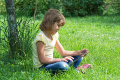 Girl in the garden with the tablet. Conducts conversation Royalty Free Stock Photo