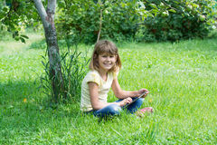 Girl in the garden with the tablet. Conducts conversation Royalty Free Stock Image