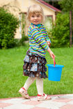 The girl in a garden with a toy bucket Stock Photos