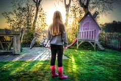 Girl in garden viewing playhouse Stock Photos