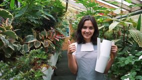 Girl gardener looks at the camera and smiles, holding a watering can for watering flowers. Girl gardener looks at the camera and smiles, holding a watering can stock video footage